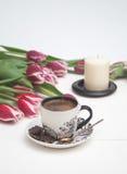 Caffè e candela in tulipani rosa Immagine Stock