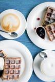 Caffè e cialde belghe su una tavola blu Immagine Stock