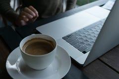 Caffè e computer portatile della sfuocatura sul fondo di legno della tavola in caffè Fotografie Stock Libere da Diritti