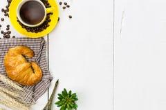 Caffè e croissant di vista superiore con il chicco di caffè Il bianco rustico corteggia immagine stock