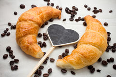Caffè e croissant su un segno in forma di cuore Fotografia Stock