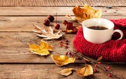 Caffè e foglie di autunno caldi su fondo di legno d'annata