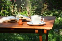 Caffè e libro in giardino Fotografie Stock