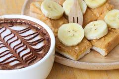 Caffè e pane tostato con burro di arachidi e la banana in caffetteria Fotografie Stock