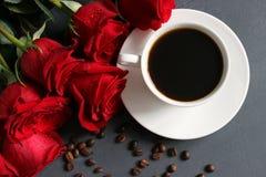 Caffè e rose, natura morta Caffè nero in una tazza bianca con un piattino sulla tavola, un mazzo delle rose rosse immagini stock libere da diritti