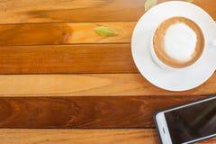 Caffè e telefono cellulare su una tavola di legno fotografie stock