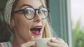 Caffè emozionale della bevanda della donna in caffè La ragazza è felice di assaggiare la bevanda delitious Fotografie Stock