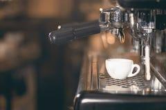 Caffè espresso bianco del caffè della tazza Macchina di caffè espresso che produce caffè, caffè espresso dorato Fotografia Stock