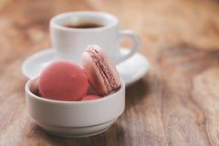 Caffè espresso con i macarons sulla tavola di legno immagini stock