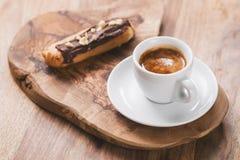 Caffè espresso con il eclair sul bordo di legno fotografia stock