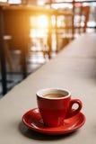 Caffè espresso rosso della tazza sul sedile di cuoio in caffè del caffè Fotografia Stock Libera da Diritti