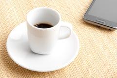 Caffè espresso scuro in una tazza vicino allo smartphone Fotografie Stock