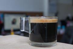 Caffè espresso in un vetro disposto su un pavimento di legno Immagini Stock Libere da Diritti