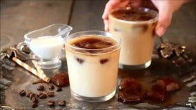 Caffè freddo ghiacciato del latte con i cubetti di ghiaccio ed i chicchi di caffè La mano della donna mette il vetro con caffè gh stock footage