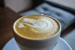 Caffè fresco e fragrante in caffetteria Una tazza del cappuccino con il disegno di un cigno Arte del Latte La bevanda d'invigorim fotografie stock