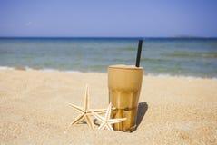 Caffè ghiacciato su un fondo della spiaggia sabbiosa Fotografia Stock