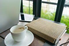 Caffè, libro del diario, computer portatile e blocco note sulla tavola in caffè Fotografia Stock Libera da Diritti