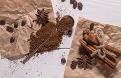 Caffè macinato, chicchi di caffè, cucchiaio d'argento, mazzo di cannella Fotografie Stock