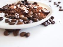 Caffè macinato del chicco di caffè di Brown e su una tazza bianca Fotografie Stock