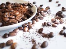 Caffè macinato del chicco di caffè di Brown e su una tazza bianca Fotografia Stock Libera da Diritti