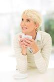 Caffè maturo della tazza della donna Immagini Stock