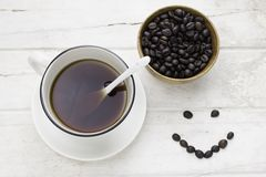 Caffè nero in chicchi bianchi di caffè e della tazza con il cucchiaio Immagine Stock Libera da Diritti