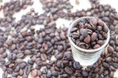 Caffè nero con un fondo dei chicchi di caffè fotografie stock libere da diritti