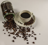 Caffè nero in una tazza bianca su un piattino con un barattolo rovesciato fotografia stock