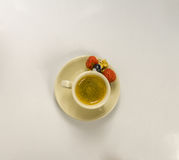 Caffè nero in una tazza di crema con la fragola succosa Fotografia Stock