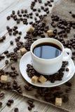 Caffè nero in una tazza e nei chicchi di caffè arrostiti su un fondo di legno Immagine Stock Libera da Diritti