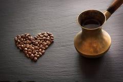 Caffè nero in vecchi chicchi di rame di caffè e del cezve sull'ardesia nera come fondo con lo spazio della copia fotografia stock libera da diritti