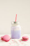 Caffè porpora in tazza stilizzata del barattolo di muratore con i macarons e la decorazione variopinta Frappè del mirtillo, cockt Fotografie Stock Libere da Diritti