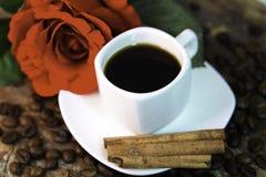 Caffè, rosa rossa, fagioli e cannella sullo scrittorio di legno Immagini Stock Libere da Diritti