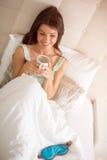 Caffè sorridente di mattina della bevanda della ragazza a letto Immagini Stock Libere da Diritti