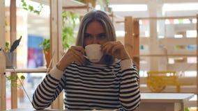 Caffè sorridente e bevente della giovane donna premurosa in caffè stock footage