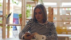 Caffè sorridente e bevente della giovane donna premurosa in caffè archivi video