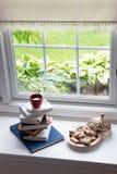 Caffè sui libri e sulle pasticcerie accatastati alla finestra Fotografia Stock Libera da Diritti