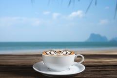 Caffè sulla tavola di legno nella spiaggia Immagini Stock