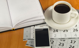 Caffè, telefono cellulare, diario e calendario sul desktop Spazio per testo immagini stock libere da diritti