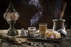 Caffè turco nel cezve e nel lukum tradizionale Vapore sopra una tazza Lampada antica immagine stock