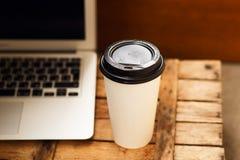 Caffè in una tazza di carta accanto al computer portatile bianco sui bordi di legno Fotografie Stock