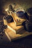 Caffè in vetro della tazza sui vecchi libri e sul pavimento di legno invecchiato immagini stock