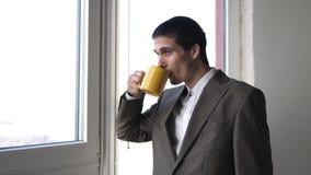 Caff? bevente del giovane uomo d'affari bello ed ammirare la finestra facente una pausa di vista in ufficio 3840x2160 video d archivio