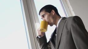 Caff? bevente del giovane uomo d'affari bello ed ammirare la finestra facente una pausa di vista in ufficio 3840x2160 stock footage