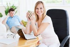 Caffè bevente della donna allegra mentre per mezzo del computer portatile Fotografia Stock