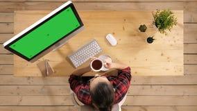 Caff? bevente della donna casuale nella stanza moderna dell'ufficio davanti al computer Esposizione verde del modello dello scher stock footage