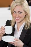 Caffè bevente della donna di affari felice in un ufficio Immagini Stock Libere da Diritti