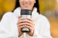 Caff? bevente della giovane donna felice nel parco di autunno immagine stock