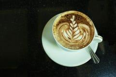 Caffè caldo in tazza e piattino e taccuino bianchi Immagini Stock