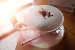 Caff?, cappuccino con una tazza bianca, latte bianco lanuginoso sulla cima Tazza e cucchiaio/composizione di caffè del cappuccino fotografia stock